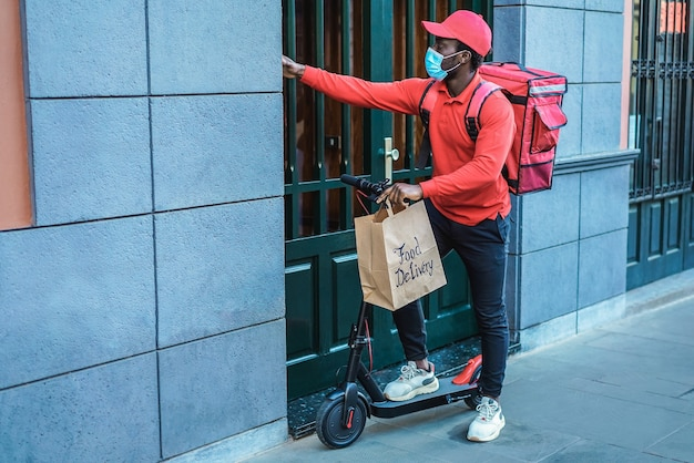 ドアベルを鳴らしている電動スクーターを持つアフリカの配達人-紙袋に焦点を当てる