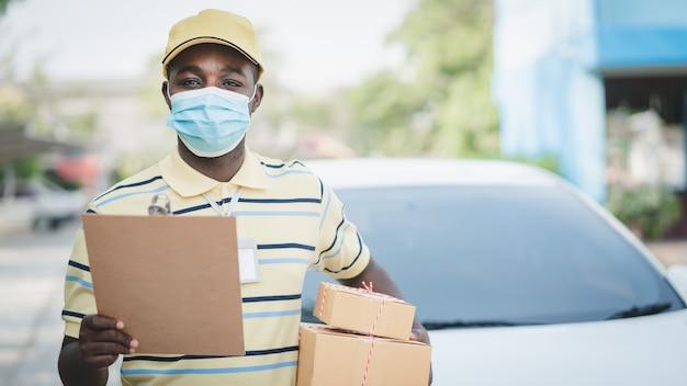 ボックスパッケージと段ボールを保持しているフェイスマスクを持つアフリカの配達人。検疫配達サービスの概念