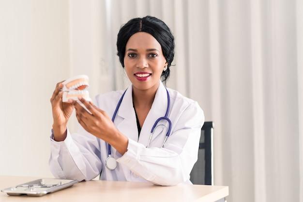 義歯を保持しているアフリカの歯科医の女性
