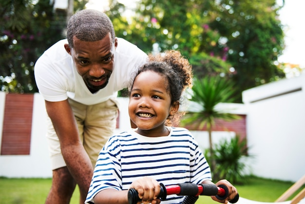 African descent father teaching daughter ride the bike