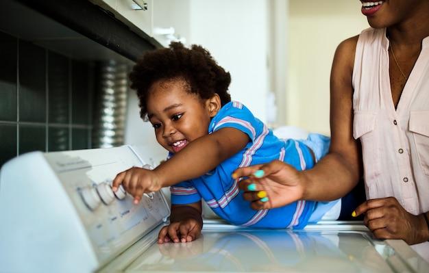 Африканский спуск малыша помогает маме делать прачечную