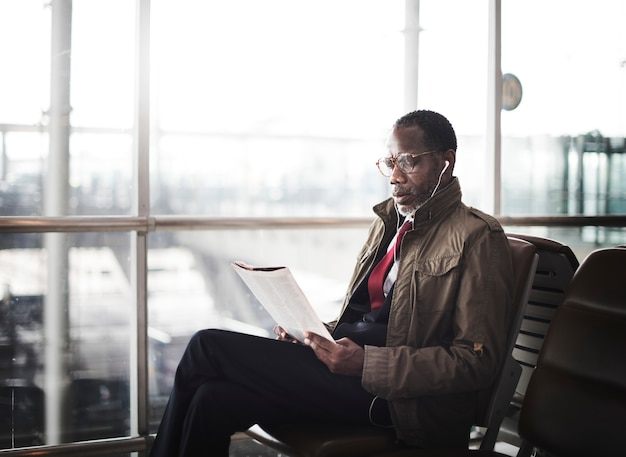 African descent man sitting reading magazine with earphones