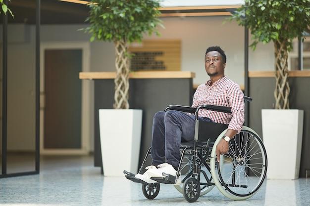 彼はオフィスビルで働いている車椅子に座っているアフリカの障害のあるビジネスマン