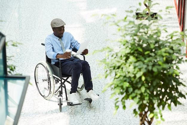 車椅子の読書文書に座って、オフィスでコーヒーを飲むアフリカの障害者実業家