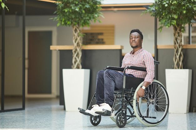 African disabled businessman sitting in wheelchair he is working at office building
