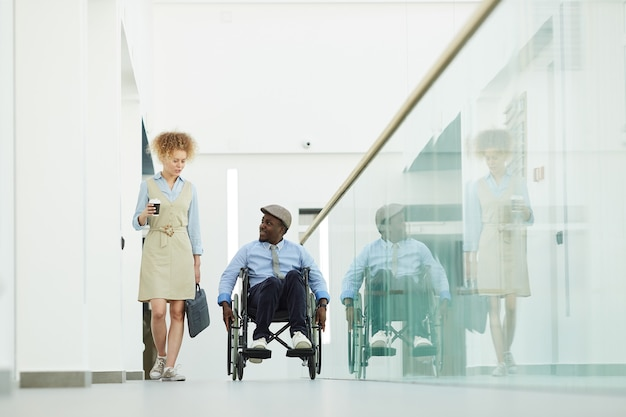 African disabled businessman in wheelchair talking to businesswoman at office corridor they working together