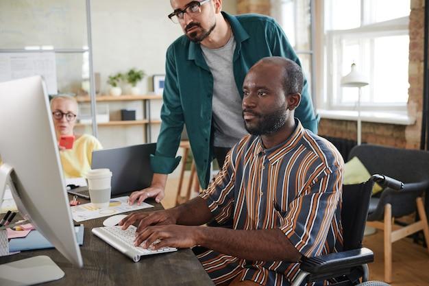 Африканский бизнесмен-инвалид, работающий за компьютером за столом, со своим партнером, наблюдающим за процессом и консультирующимся с ним