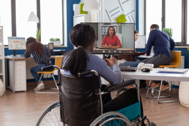 African disabled handicapped businesswoman sitting immobilized in wheelchair talking with remote partner on video call from startup business office