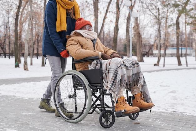 Африканский инвалид, сидящий в инвалидной коляске, гуляет в зимний день вместе со своим помощником