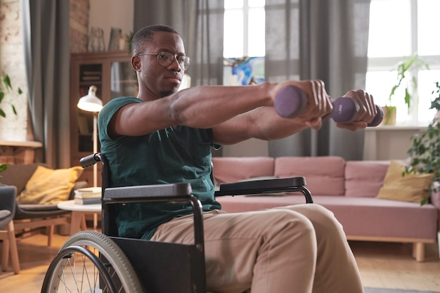 African disabled man sitting in wheelchair and exercising with dumbbells at home