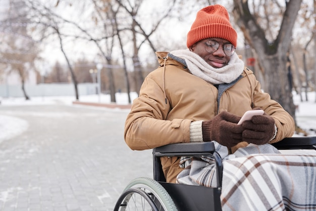 Африканский инвалид печатает сообщение на мобильном телефоне, сидя на свежем воздухе в зимний день