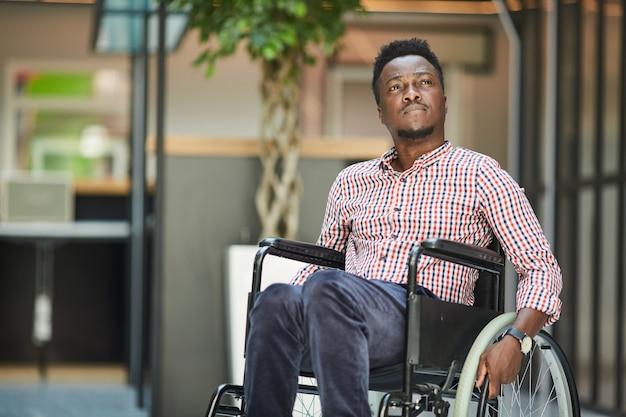 彼はオフィスビルにいる車椅子に座っているアフリカの障害のあるサラリーマン