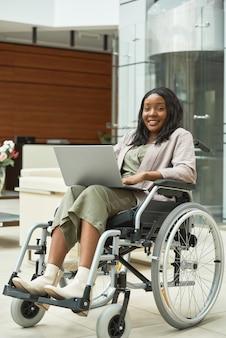 オフィスでのオンライン作業のためにラップトップを使用して車椅子のアフリカの障害のある女性