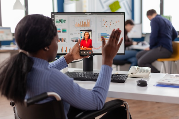 African disabled worker waving at online partner during video call sitting immobilized in wheelchair...