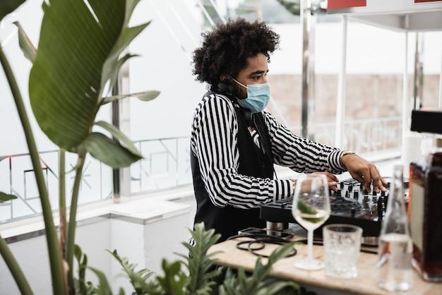 Африканский диджей играет музыку в коктейль-баре на открытом воздухе в защитной маске - сосредоточьтесь на лице