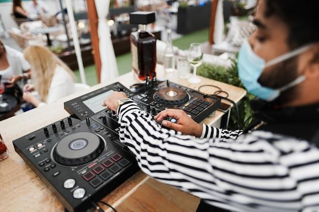 Африканский диджей играет музыку в коктейль-баре на открытом воздухе в защитной маске - сосредоточьтесь на правой руке