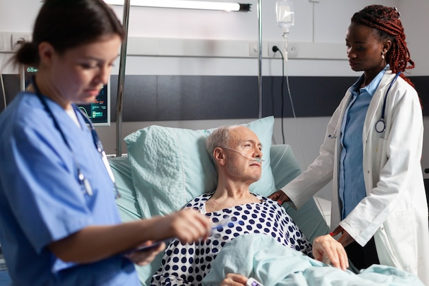 African doctor in hospital room discussing with sick senior man