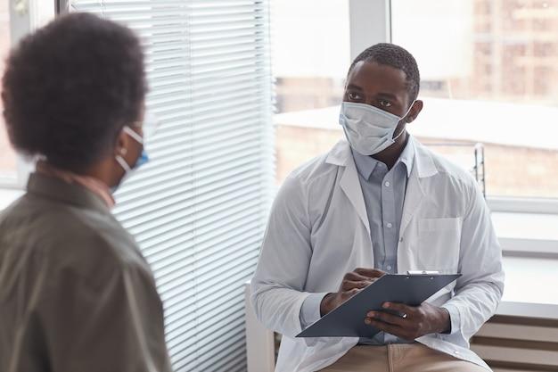 보호 마스크를 쓴 아프리카 의사가 병원을 방문하는 동안 환자와 이야기를 나누고 있다