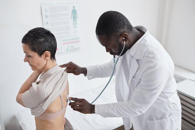 병원을 방문하는 동안 환자의 심장 박동을 듣고 있는 아프리카 의사