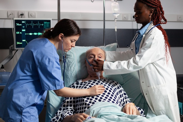 African doctor and medical assistant helping senior man breath using oxygen mask, in hospital laying in bed