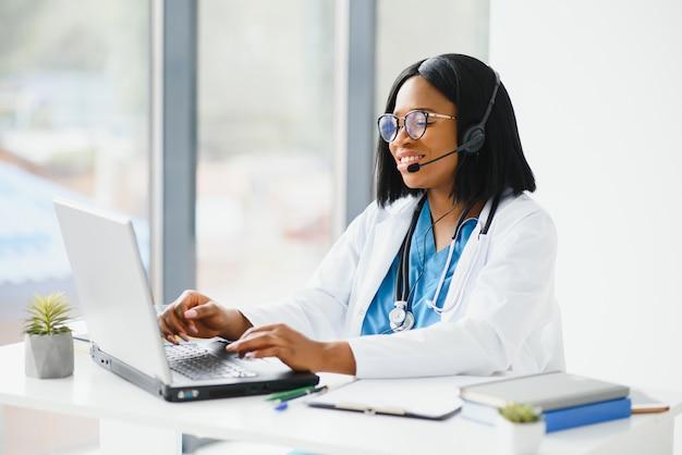 アフリカの医師はヘッドセットを着用し、患者に相談してノートパソコンの画面でオンラインウェブカメラのビデオ通話を行います。