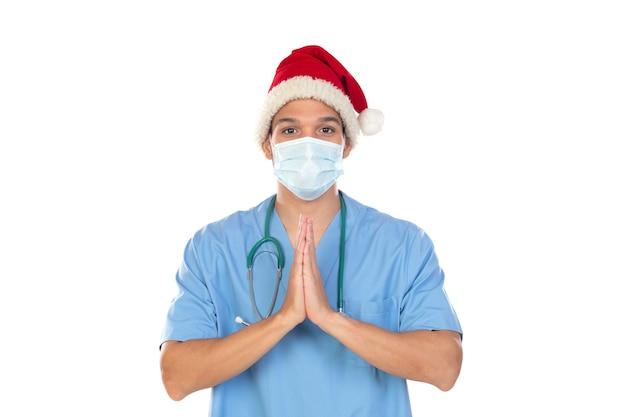 Африканский врач в рождественской шапке во время коронавируса изолирован на белой стене