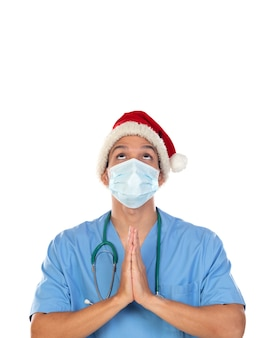African doctor wearing a christmas hat at coronavirus time isolated on a white wall Premium Photo