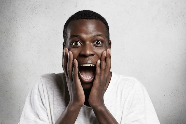 African employee or customer with shocked and surprised face, looking and screaming with big eyes and mouth wide open, holding hands on his cheeks.