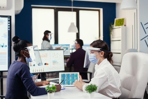 Covid19に対してフェイスマスクを着用して職場の机に座っているマネージャーと話し合っているアフリカの従業員。新しいとクリエイティブなオフィスで一緒に働いてコミュニケーションしているビジネスマンの多様なグループ
