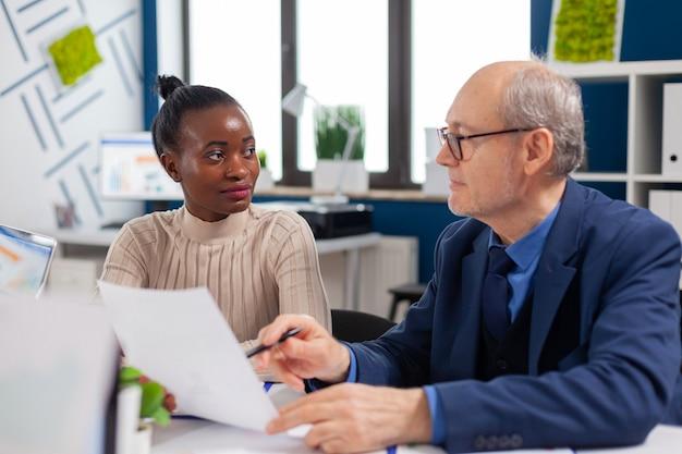 Impiegato africano che discute con un dirigente senior alla ricerca di grafici finanziari nella sala riunioni della società di avvio