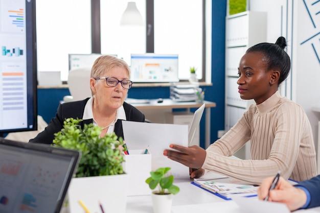 プロジェクト文書の分析を探している上級起業家投資家と話している金融ビジネスボード会議室のアフリカの従業員