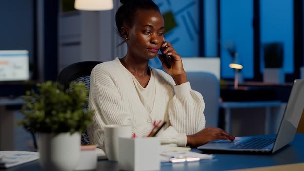 늦은 밤 노트북에서 일하는 동안 전화로 말하는 아프리카 직원