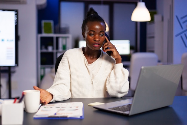 African employee speaking at phone while working at laptop late at night