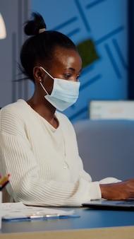 노트북 초과 근무를 하는 보호용 안면 마스크를 쓴 아프리카 직원