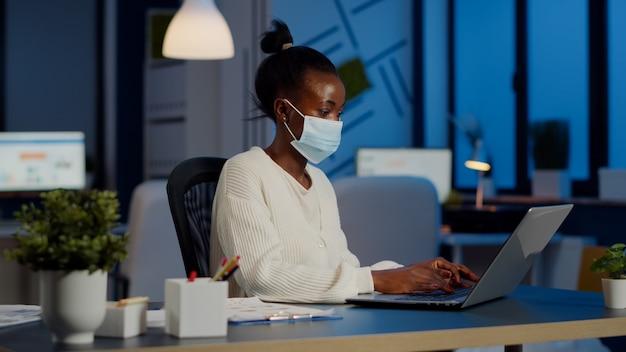 Impiegato africano con maschera protettiva che lavora al laptop per gli straordinari nel nuovo normale ufficio commerciale per rispettare la scadenza del progetto, analizzando i documenti seduti alla scrivania durante la pandemia globale