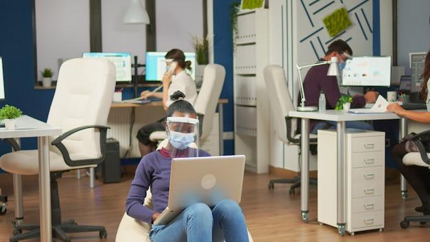 바이저와 얼굴 마스크를 쓴 아프리카 직원은 노트북 작업을 하는 사무실 한가운데 빈백에 앉아 있습니다. 다민족 비즈니스 팀은 사회적 거리를 존중하는 회사 전략을 계획합니다.