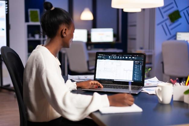 ビジネスオフィスで働くcadプログラムの新しいbluilding計画を分析するアフリカのエンジニアコンストラクターデザイナーアーキテクト