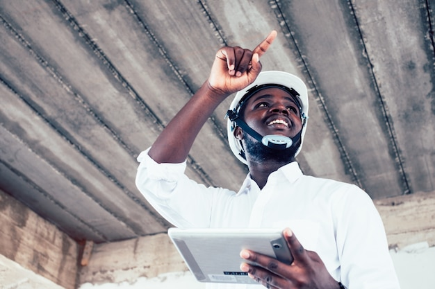 アフリカのエンジニア男建築家探しているとタブレットの建設プロジェクト