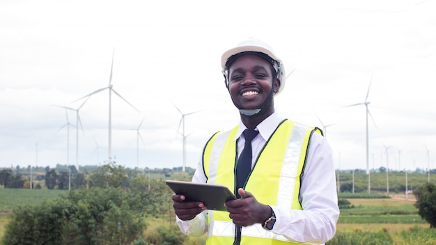 African engineer standing and hoding laptop with wind turbine