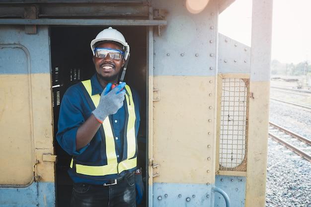 아프리카 엔지니어는 무선 통신이나 무전기로 대화하는 동안 사고를 방지하기 위해 보안경, 헬멧, 장갑을 착용합니다.