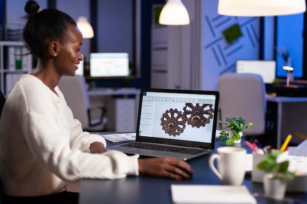 African engineer working late at night on a 3d model of industrial gears at laptop doing overtime in start up office