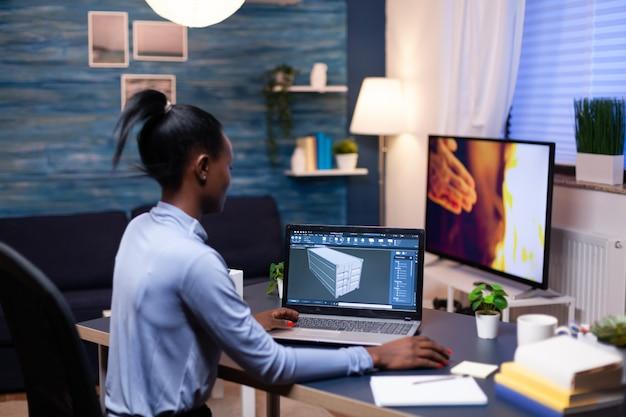 늦은 밤 홈 오피스에서 일하는 아프리카 기업가 개발자. 장치 디스플레이에 소프트웨어를 보여주는 개인용 컴퓨터에서 프로토타입 아이디어를 연구하는 산업 흑인 여성 엔지니어