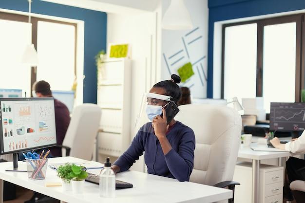 フェイスマスクを着用して職場に座っているコロナウイルスの間にビジネスコールを持っているアフリカの起業家。金融会社で社会的距離を尊重して働く多民族の同僚。