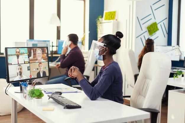 フェイスマスクを身に着けているcovid19の間にビデオ会議を持っているアフリカの起業家