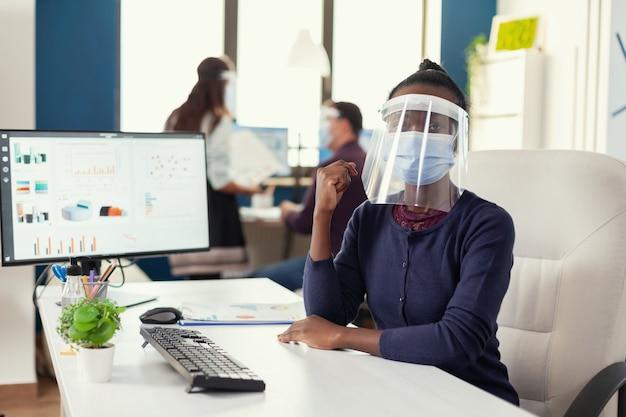 マスクとフェイスシールドアガシントコロナウイルスを身に着けているオフィスでアフリカの起業家。世界的大流行の際の社会的距離を尊重する金融会社で働く多民族のビジネスチーム。