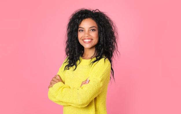 黄色のニットのスウェットシャツで漆黒のウェーブのかかった髪を持つアフリカの民族の女性は、カメラを見て、喜びで笑っている間ポーズをとっています