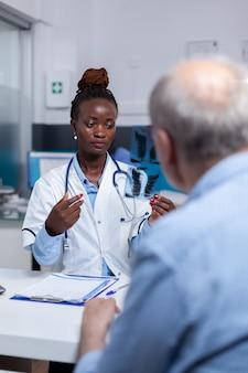 X線スキャンを見ている医者の仕事を持つアフリカの民族の女性