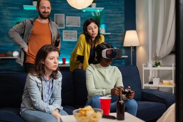 Африканка переживает виртуальную реальность, играя в видеоигры, пока ее друзья общаются. группа людей смешанной расы гуляет вместе, развлекаясь поздно ночью в гостиной.