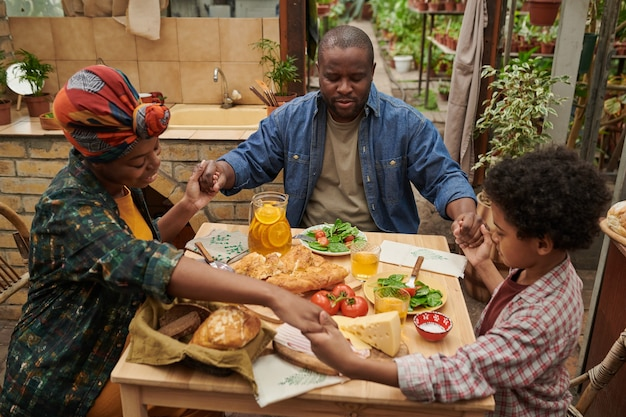 African family sitting at the table and praying during dinner in the garden