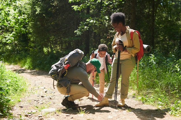 African family of three with backpacks and sticks travelling together in the forest